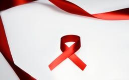 Det röda bandet gömma i handflatan på Royaltyfri Foto