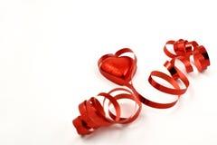 Det röda bandet med ett chokladhjärtamateriel avbildar Royaltyfri Foto