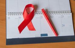 Det röda bandet på kalendern som lyfter medvetenhet mot HJÄLPMEDEL, kopierar utrymme Royaltyfria Foton
