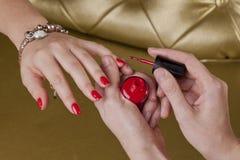 Det röda fingret spikar i en kosmetisk mitt Royaltyfria Foton