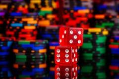 Det röda kasinobegreppet tärnar på bakgrund av en defocused flerfärgad uppsättning av chiper royaltyfri bild