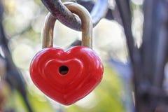 Det röda låset i form av en hjärta hänger på en järnstång arkivbilder