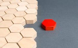 Det röda objektet kopplas från från andra objekt sexh?rningar Begreppet av att avskilja delar från hela eller förbindande delar t royaltyfri foto