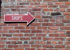 Det röda piltecknet på en tegelstenvägg som pekar, shoppar Arkivfoton