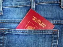Det röda ryska passet i den tillbaka jeansen stoppa i fickan Royaltyfria Foton