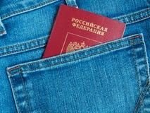 Det röda ryska passet i den tillbaka jeansen stoppa i fickan Royaltyfri Bild