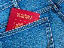 Det röda ryska passet i den tillbaka jeansen stoppa i fickan Royaltyfri Foto