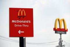 Det röda tecknet av McDonald drev igenom på dagsljus och fokuserar ut dicutstil av logoen för McDonald ` s royaltyfri foto