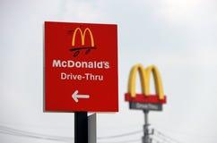 Det röda tecknet av McDonald drev igenom på dagsljus och fokuserar ut dicutstil av logoen för McDonald ` s royaltyfri fotografi