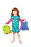 Det rödhåriga barnet med shoppingpåsar royaltyfri bild