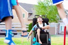 Det rörelsehindrade barnet i hållande ögonen på barnlek för rullstol på parkerar Royaltyfri Bild