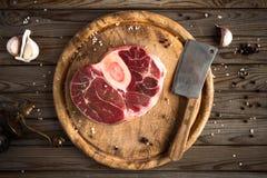 Det rå nya korset klippte kalvköttet med vitlök, peppar och smaktillsatser på träskärbräda med slaktareköttyxan Royaltyfri Foto