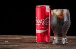 Det redaktörs- fotoet av coca-cola exponeringsglas med is och kan på trätabell- och kopieringsutrymme på svart för bildfoto för k Royaltyfri Bild