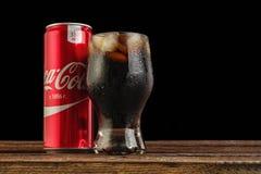 Det redaktörs- fotoet av coca-cola kan med exponeringsglas av cola med is Arkivbilder