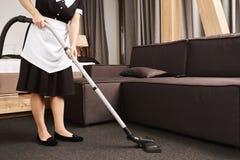 Det rena huset är nyckel- för produktivitet Kantjusterat skott av husan under arbete, rengörande vardagsrum med dammsugare royaltyfria foton