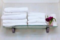 Det rena vita badrummet för handdukhängarehyllan blommar rosa tulpan royaltyfria foton