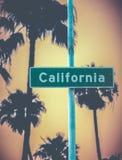 Det Retro Kalifornien tecknet och gömma i handflatan fotografering för bildbyråer