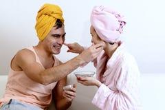 Det roliga älska paret att bry sig för huden Att sitta på soffan i handdukar och orsakar sig leramaskeringen på framsidan Hälsovå Royaltyfria Foton