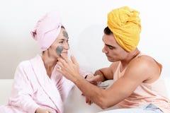 Det roliga älska paret att bry sig för huden Att sitta på soffan i handdukar och orsakar sig leramaskeringen på framsidan Hälsovå Arkivfoto