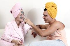 Det roliga älska paret att bry sig för huden Att sitta på soffan i handdukar och orsakar sig leramaskeringen på framsidan Hälsovå Arkivbilder