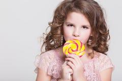 Det roliga barnet äter godisklubban, lilla flickan som äter sötsaker, studio Arkivfoto