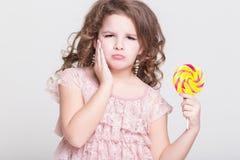 Det roliga barnet äter godisklubban, lilla flickan som äter sötsaker, studio Arkivfoton