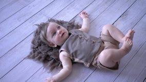 Det roliga barnet ligger och vrida sig ben på trägolv arkivfilmer
