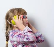 Det roliga barnet lyssnar till musik Royaltyfri Foto
