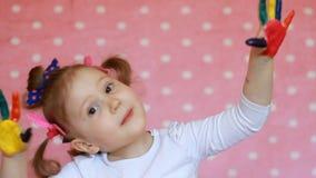 Det roliga barnet med gömma i handflatan i mångfärgad målarfärg Lycklig liten flicka med målade smutsiga händer arkivfilmer