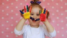 Det roliga barnet med gömma i handflatan i mångfärgad målarfärg Lycklig liten flicka med målade smutsiga händer lager videofilmer