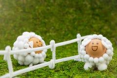 Det roliga fåret figurerar ägg med ett staket på grön mossig bakgrund, Arkivfoto