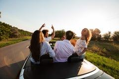 Det roliga företaget av lyckliga unga flickor och grabbar sitter i en svart cabrioletväg på en solig dag fotografering för bildbyråer