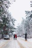 det roliga företaget med behandla som ett barn lite på en snöig väg under vinter sörjer Royaltyfri Fotografi