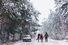 det roliga företaget med behandla som ett barn lite på en snöig väg under vinter sörjer Fotografering för Bildbyråer