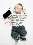 Det roliga fotoet av behandla som ett barn pojken som lyssnar till musik på telefonen med earphon Royaltyfri Fotografi