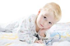 Det roliga gulliga lilla barnet i pyjamas med blont hår ligger på en säng Royaltyfri Fotografi