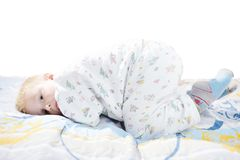 Det roliga gulliga lilla barnet i pyjamas med blont hår ligger på en säng Royaltyfria Bilder