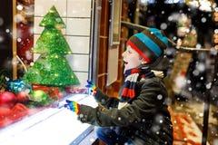 Det roliga lyckliga barnet i modevinter beklär danandefönstershopping som dekoreras med gåvor, xmas-träd Royaltyfri Foto