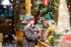 Det roliga lyckliga barnet i modevinter beklär danandefönstershopping som dekoreras med gåvor, xmas-träd Royaltyfria Bilder