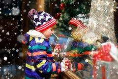 Det roliga lyckliga barnet i modevinter beklär danandefönstershopping som dekoreras med gåvor, xmas-träd Royaltyfri Fotografi