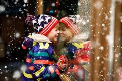 Det roliga lyckliga barnet i modevinter beklär danandefönstershopping som dekoreras med gåvor, xmas-träd Royaltyfri Bild