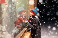 Det roliga lyckliga barnet i modevinter beklär danandefönstershopping som dekoreras med gåvor, xmas-träd Arkivfoton