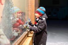 Det roliga lyckliga barnet i modevinter beklär danandefönstershopping som dekoreras med gåvor, xmas-träd Arkivfoto