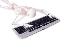 Det roliga skelett- arbetet på datoren Arkivfoto