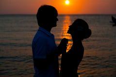 Det romantiska barn kopplar ihop solnedgångsilhouetten på strand. Arkivbilder