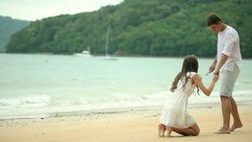 Det romantiska barnet kopplar ihop attraktionhjärtaformer i sanden på stranden lager videofilmer