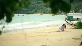 Det romantiska barnet kopplar ihop attraktionhjärtaformer i sanden på stranden arkivfilmer