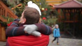 Det romantiska datummärkningparet på julen mässan, man roterar hans kramade flickvän omkring, Xmas-trädet är i stock video