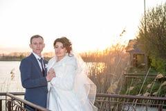 Det romantiska landskapet, nygift personparet som poserar på solnedgången nära floden, brudgummen, rymmer handen av en brud arkivbilder