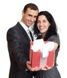 Det romantiska paret med gåvaasken, den iklädda svarta dräkten för folk, man ger gåvan till kvinnan som isoleras på vit bakgrund Royaltyfria Bilder